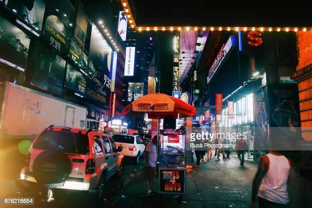 Night street scene in Midtown Manhattan: nuts food cart along 42nd Street. New York City, USA