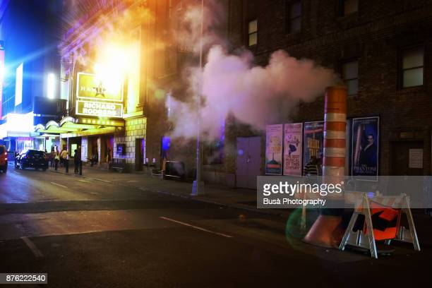 Night street scene in Midtown Manhattan: street smoke stack with steam coming out and the Richard Rodgers Theater at West 46th Street. New York City, USA