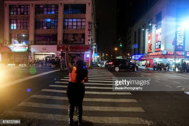 Night street scene in Midtown Manhattan: Woman hailing a taxi cab along 8th Avenue. New York City, USA
