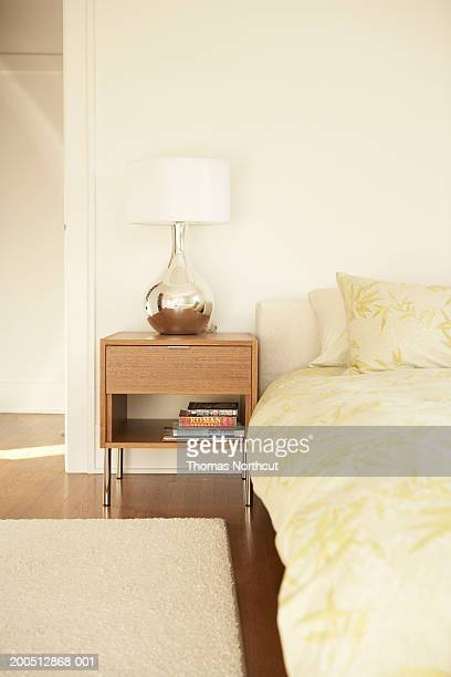 Night table and lamp beside bed