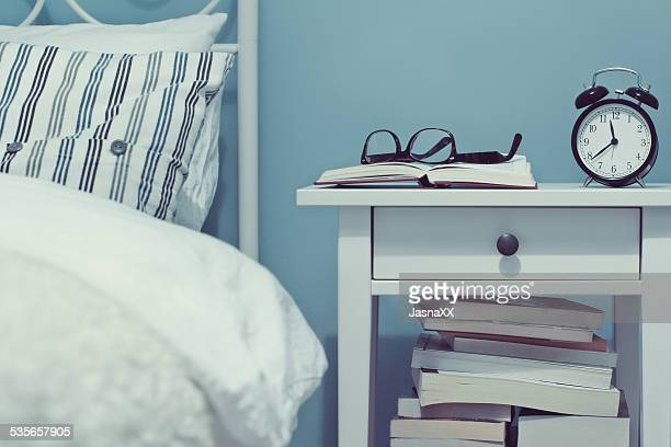 View of night table with book and alarm clock
