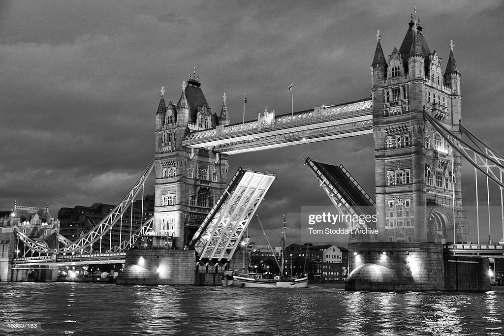 A night time view of Tower Bridge raised over the River Thames during a high tide. The bridge was built between 1886 and 1894 and named after the Tower of London which is nearby. Crossing below the bridge is the sailing barge SB Will that famously caused the bridge to be raised unexpectedly when President Bill Clinton and his motorcade were due to cross in May 1997 after having dinner with Primeminister Tony Blair in a nearby restaurant.