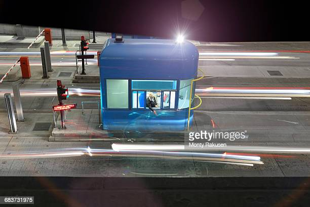 Night view of cars passing through toll booth at bridge, high angle