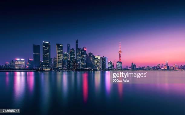 Night view of illuminated modern skyscrapers reflected in Huangpu River, Lujiazui, Shanghai, China