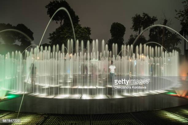 Night view of modern colorful fountains in a public park.