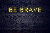 Night view of neon sign with text be brave.
