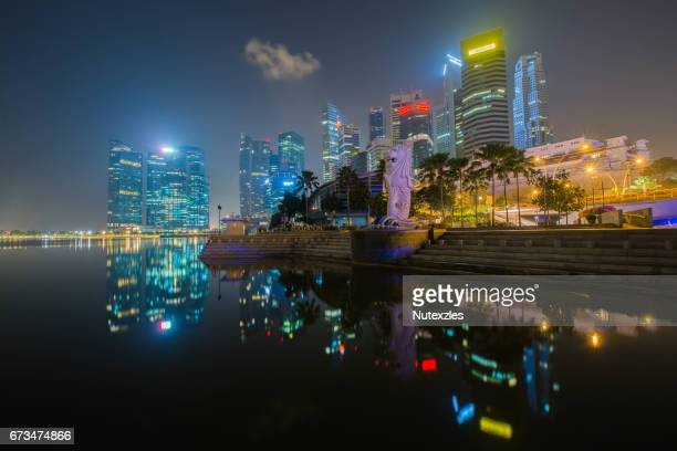 Night view of Singapore Merlion at Marina Bay against Singapore skyline. Merlion is a well-known tourist icon, mascot and national personification of Singapore