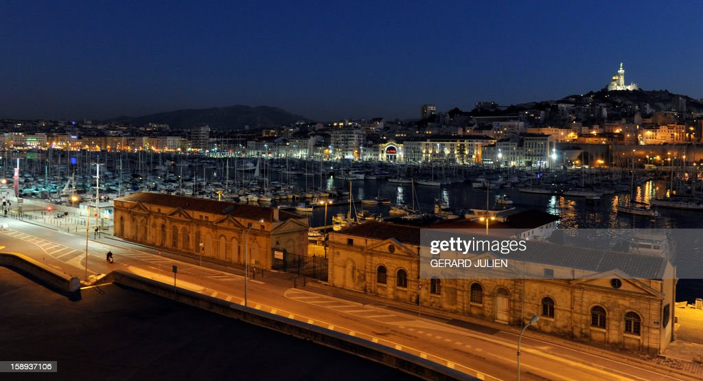 Night view taken on January 03, 2013 of the 'Vieux-Port' (Old Harbour) in the French southern city of Marseille, one week ahead of the 2013 'Marseille-Provence European Capital of Culture' event. In the background, at right, is seen the Notre-Dame de la Garde basilica.