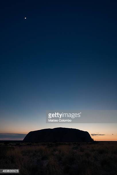 CONTENT] Night with small moon over Uluru just before sunrise in the red sand desert landscape of Northern Territory Australia Uluru also known as...