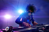 nightclub dj playing music on deck with vinyl record headphones light flare clubbing party scene