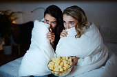 Scared girls hiding in blanket while watching horrors on TV at night