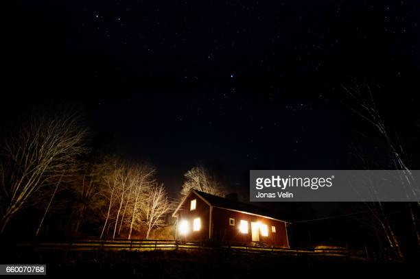 Nightphoto of stars and a house lit up in the background.