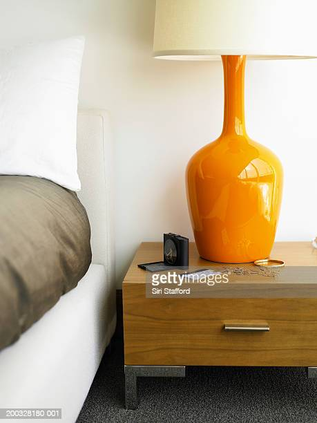 Nightstand with alarm clock, hotel keycard and jewelry