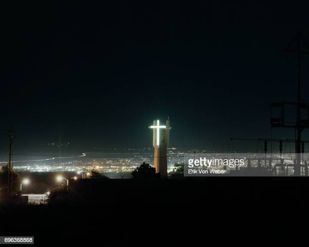 nighttime cityscape of illuminated neon cross on steeple of church