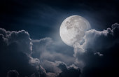 Attractive photo of a nighttime sky with clouds, bright full moon would make a great background. Nightly sky with large moon. Beautiful nature use as background. Outdoors.