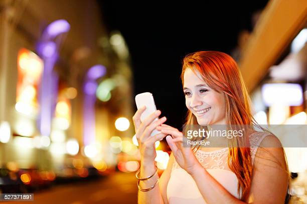 Nighttime street lights show beautiful blonde busy texting on smartphone