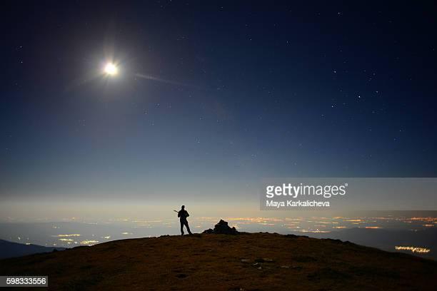 Nighttime tambura player standing on top of the world