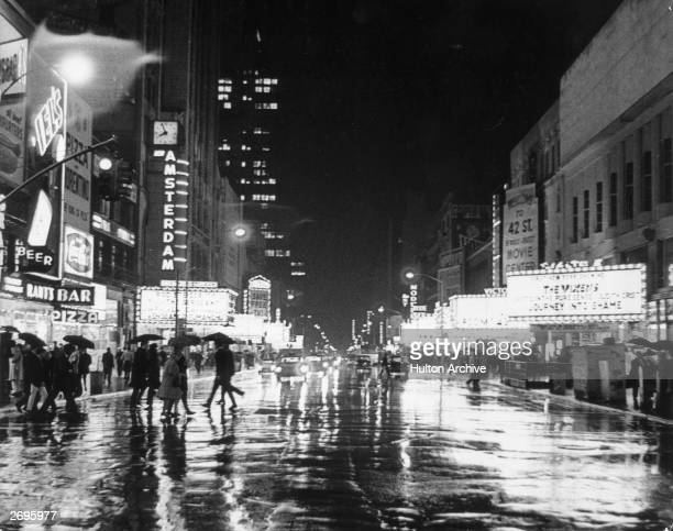 Nighttime view of 42nd Street in the rain with illuminated theater marquees and neon signs Time Square New York City Pedestrians carry umbrellas...