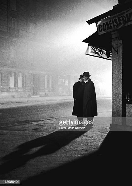 Nighttime view of a couple as they stand in front of a candy shop on a misty street corner Paris Evening Paris France 1934