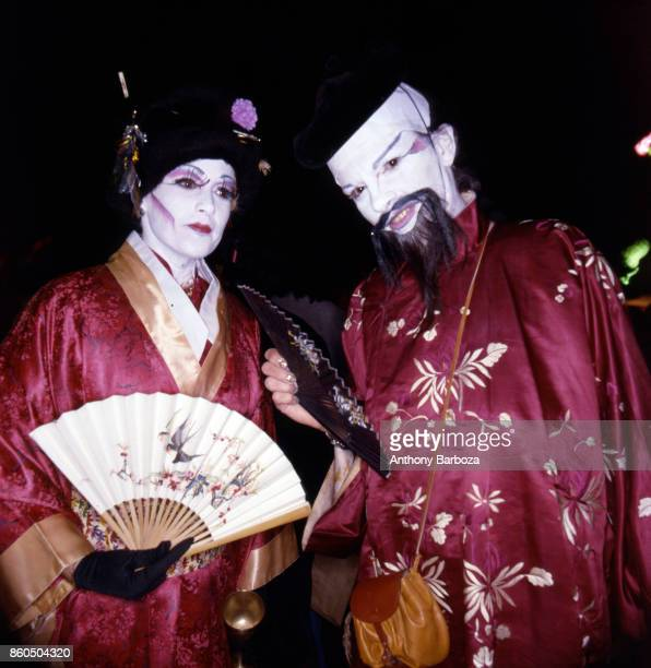 Nighttime view of a couple in matching costumes including kimonos white face paint and fans during the annual Halloween Parade New York New York late...