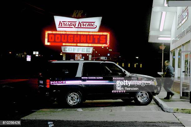 Nighttime view of a Fairfax County police vehicle parked outside a Krispy Kreme donut shop Alexandria Virginia September 13 1998 An unidentified...
