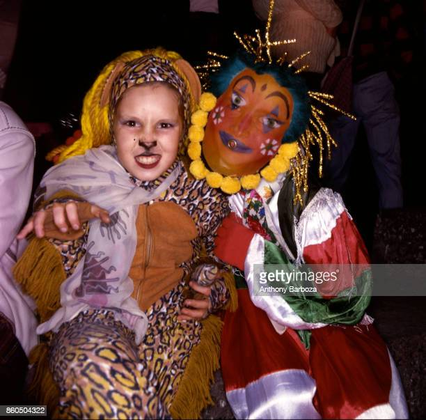 Nighttime view of a pair of participants one dressed in fringed leopard print and the other in a harlequin costume and mask during the annual...