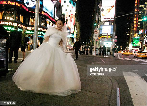 A nighttime view of a unidentified Asian woman in a bridal gown posing for photographs Times Square Manhattan New York May 4 2004