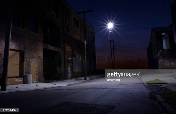 Nighttime view of an empty side street under a streetlight