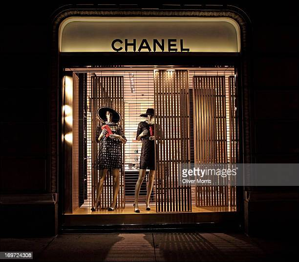 Nighttime view of an illuminated window display of women's summer fashions at the Chanel clothing store Manhattan's Upper East Side neighborhood New...