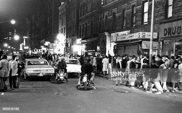Nighttime view of pedestrians and cars on MacDougal Street in Greenwich Village New York New York May 21 1966 In the center is the awning of Cafe Wha