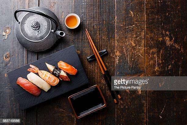 Nigiri sushi set and green tea on wooden table