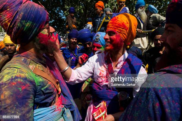 Nihang men smear colors on one another's face during Hola Mohalla festival Hola Mohalla is a threeday festival started by the tenth Sikh Guru Govind...