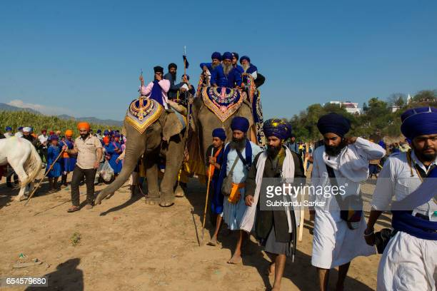 Nihang Sikhs ride on elephants during Hola Mohalla festival Hola Mohalla is a threeday festival started by the tenth Sikh Guru Govind Singh for the...