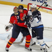 Nik Antropov of the Winnipeg Jets and Filip Kuba of the Florida Panthers battle for position in front of goaltender Jose Theodore of the Florida...