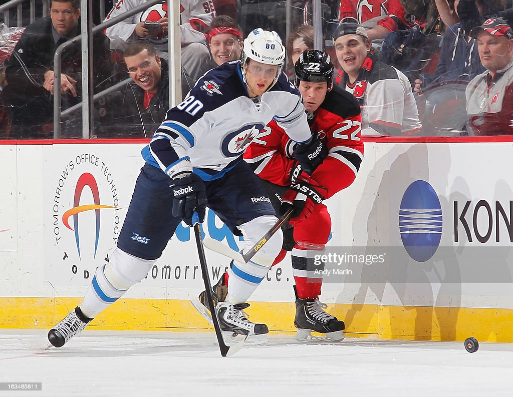 Nik Antropov #80 of the Winnipeg Jets and Krystofer Barch #22 of the New Jersey Devils battle for control of the puck during the game at the Prudential Center on March 10, 2013 in Newark, New Jersey.
