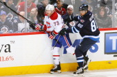 Nik Antropov of the Winnipeg Jets bumps Michael Ryder of the Montreal Canadiens along the boards as the puck flies by during first period action at...
