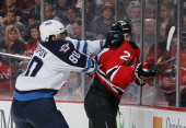 Nik Antropov of the Winnipeg Jets hits Mark Fayne of the New Jersey Devils into the boards at the Prudential Center on January 17 2012 in Newark New...
