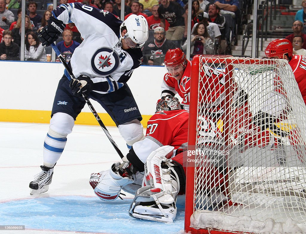 <a gi-track='captionPersonalityLinkClicked' href=/galleries/search?phrase=Nik+Antropov&family=editorial&specificpeople=202953 ng-click='$event.stopPropagation()'>Nik Antropov</a> #80 of the Winnipeg Jets plays the puck in front of <a gi-track='captionPersonalityLinkClicked' href=/galleries/search?phrase=Cam+Ward&family=editorial&specificpeople=453216 ng-click='$event.stopPropagation()'>Cam Ward</a> #30 of the Carolina Hurricanes during an NHL preseason game on September 25, 2011 at Time Warner Arena in Charlotte, North Carolina.