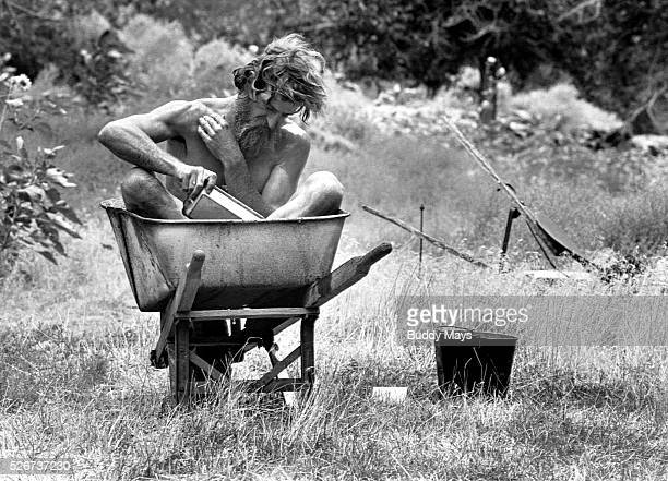 Nik Hogan the 'hermit of Desolation Canyon' bathes himself in a wheelbarrow The wheelbarrow is filled with water from the creek which is then allowed...