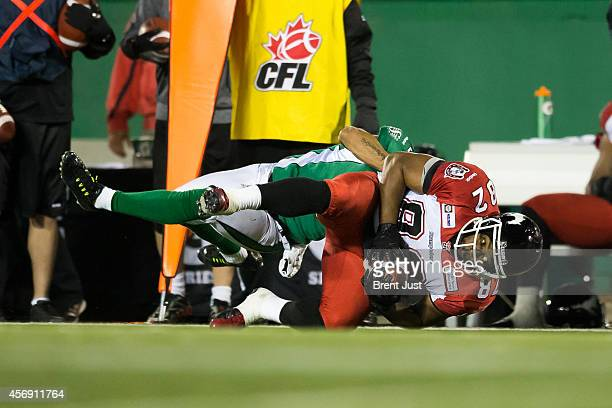 Nik Lewis of the Calgary Stampeders is tackled by Macho Harris of the Saskatchewan Roughriders after a catch in a game between the Calgary Stampeders...