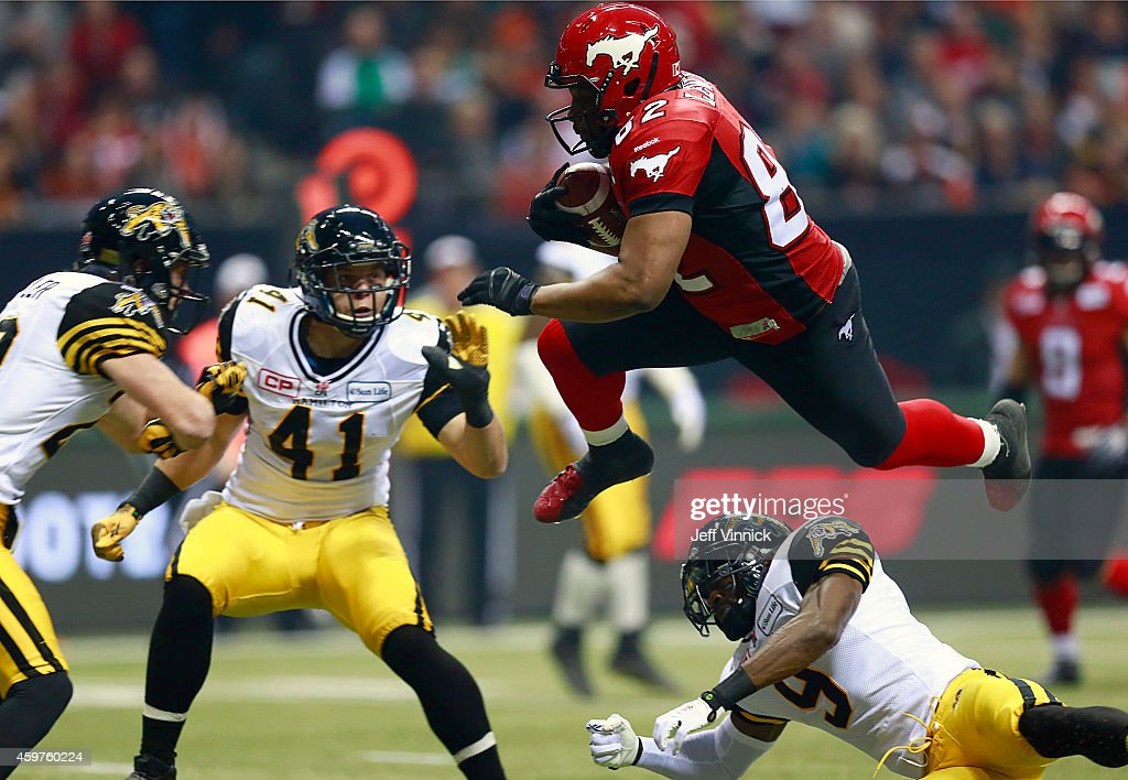 Nik Lewis of the Calgary Stampeders leaps open Brandon Stewart and into Erik Harris and Craig Butler of the Hamilton TigerCats during the 102nd Grey...