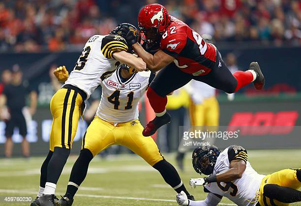 Nik Lewis of the Calgary Stampeders runs headlong into Craig Butler of the Hamilton TigerCats during the 102nd Grey Cup Championship Game at BC Place...