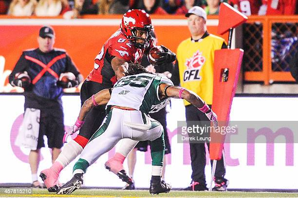 Nik Lewis of the Calgary Stampeders runs with the ball as Weldon Brown of the Saskatchewan Roughriders looks to stop him during a CFL game at McMahon...