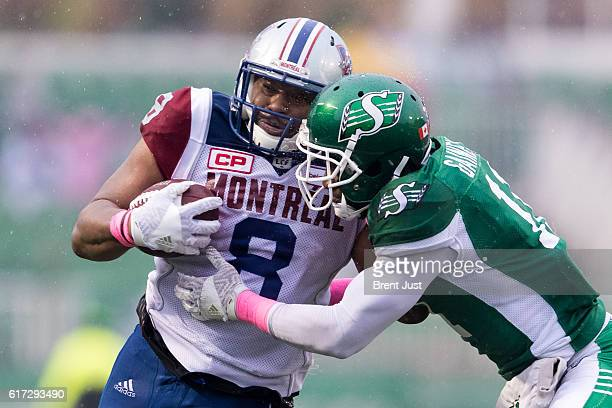 Nik Lewis of the Montreal Alouettes fights off a tackle from Ed Gainey of the Saskatchewan Roughriders in the game between the Montreal Alouettes and...