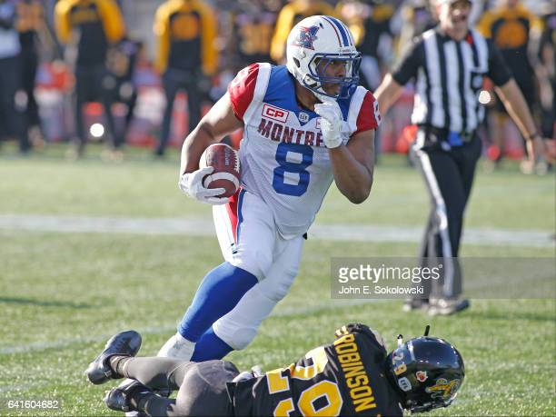 Nik Lewis of the Montreal Alouettes gains yards after knocking down Jermaine Robinson of the Hamilton TigerCats during a CFL game at Tim Hortons...