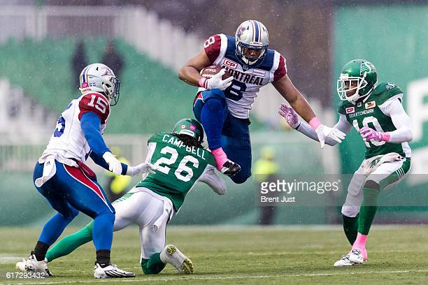Nik Lewis of the Montreal Alouettes leaps over Tevaughn Campbell of the Saskatchewan Roughriders during a run in the game between the Montreal...