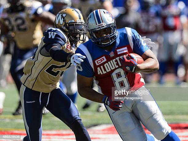 Nik Lewis of the Montreal Alouettes sidesteps Bruce Johnson of the Winnipeg Blue Bombers during the CFL game at Percival Molson Stadium on September...