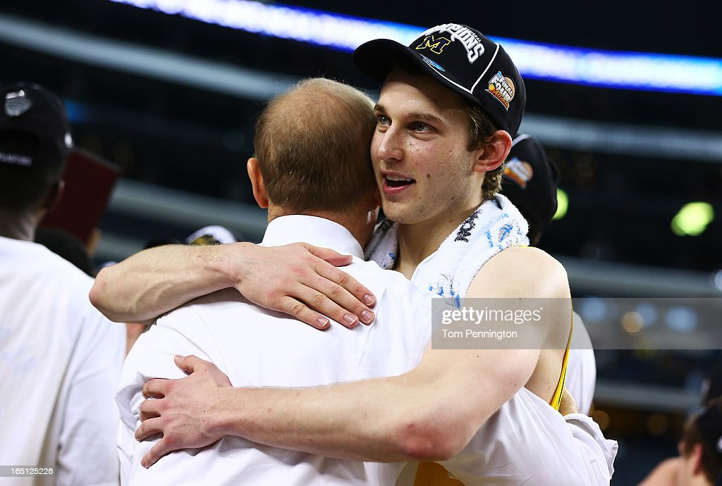 Nik Stauskas #11 hugs head coach John Beilein of the Michigan Wolverines after their 79 to 59 win over the Florida Gators during the South Regional Round Final of the 2013 NCAA Men's Basketball Tournament at Dallas Cowboys Stadium on March 31, 2013 in Arlington, Texas.