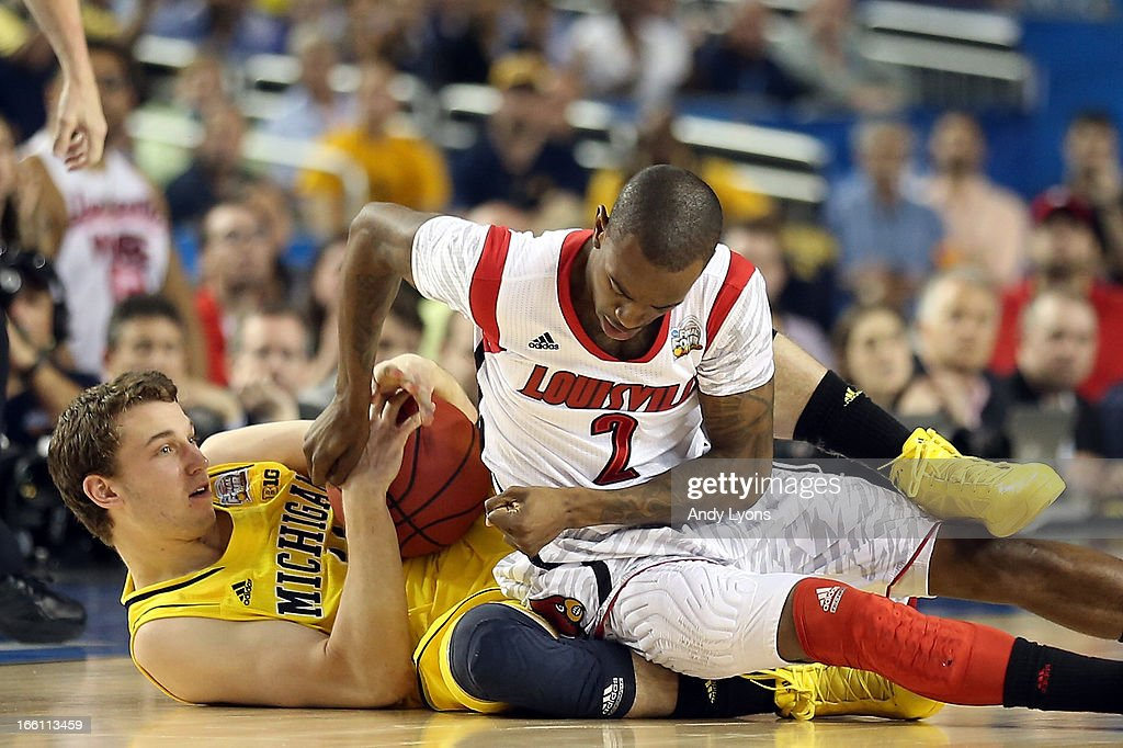 Nik Stauskas #11 of the Michigan Wolverines and Russ Smith #2 of the Louisville Cardinals battle for a loose ball in the second half during the 2013 NCAA Men's Final Four Championship at the Georgia Dome on April 8, 2013 in Atlanta, Georgia.