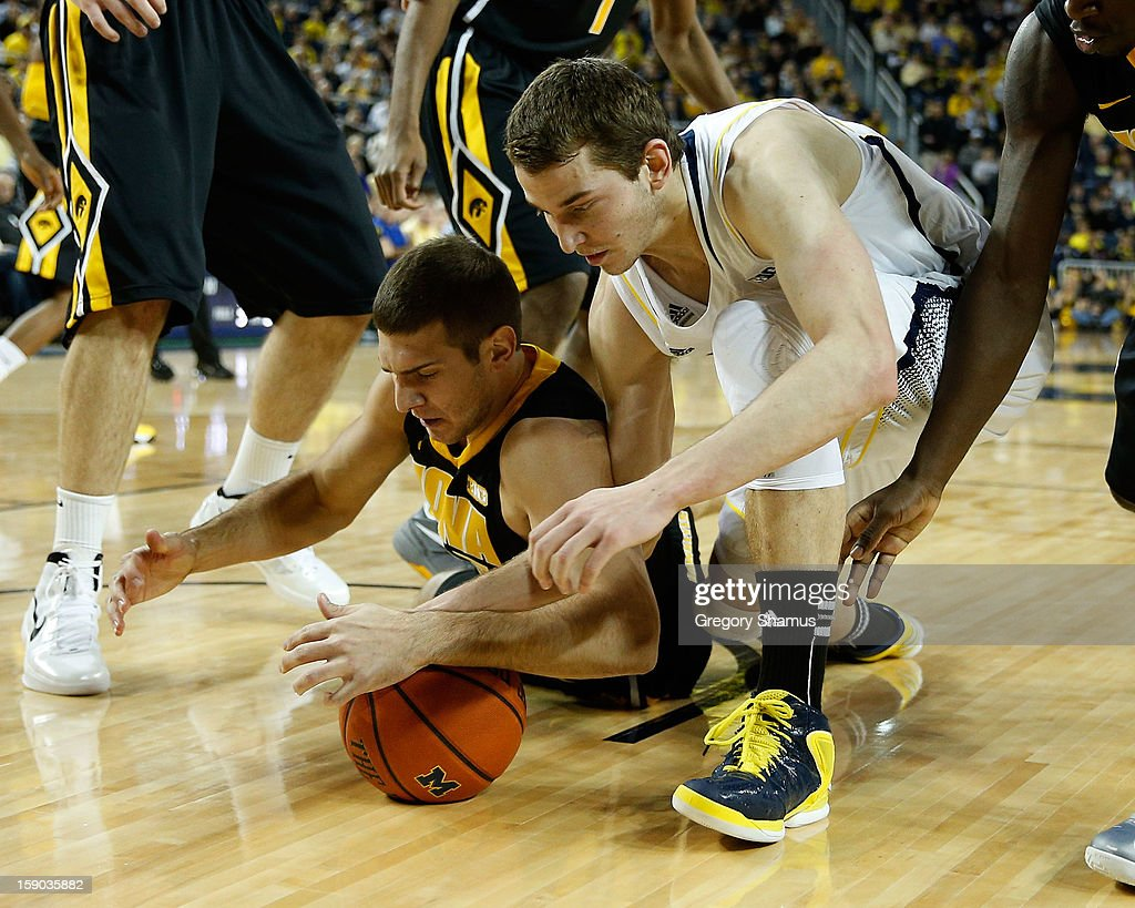 Nik Stauskas #11 of the Michigan Wolverines dives for the ball along with Eric May #25 of the Iowa Hawkeyes at Crisler Center on January 6, 2013 in Ann Arbor, Michigan.
